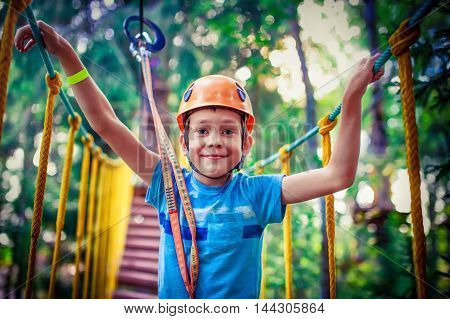 happy boy on the zip line. proud of his courage the child in the high wire park
