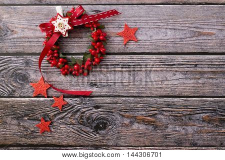 Closeup of red christmas stars and wreath over wooden background