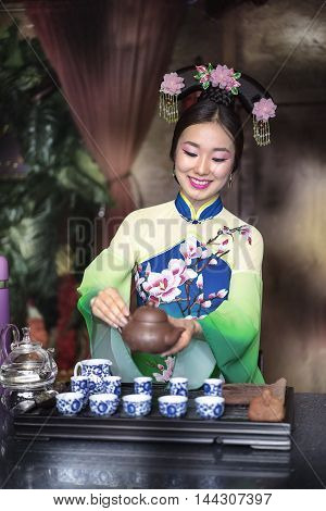 A young girl in a tradition dress holds a Chinese tea ceremony
