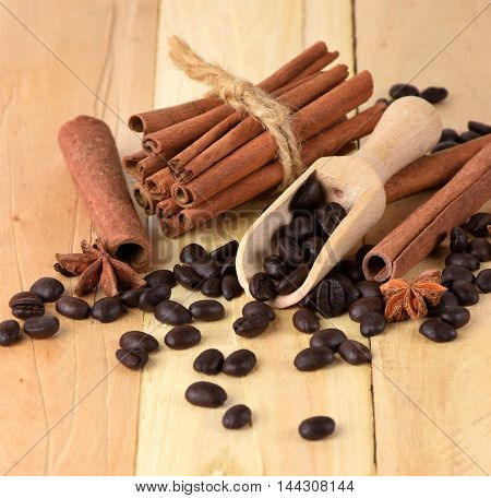Fragrant cinnamon sticks star anise and coffee beans on the wooden background. Christmas flavors. The festive mood Close-up./select focus/