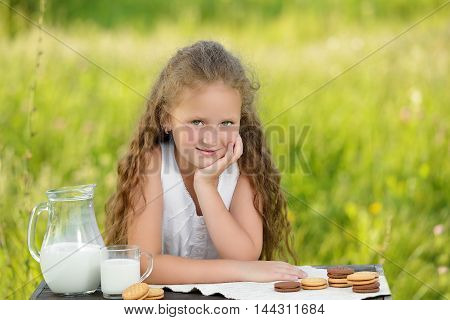 Little cute girl drinking a glass of milk in garden. Adorable curly kid having breakfast. Summer time. Healthy lifestyle