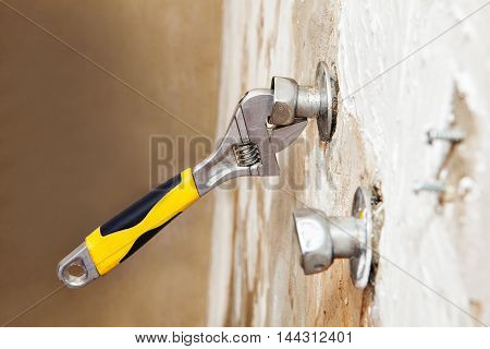 Closeup wall mount faucet eccentric adjusts position with plumbers adjustable wrench.