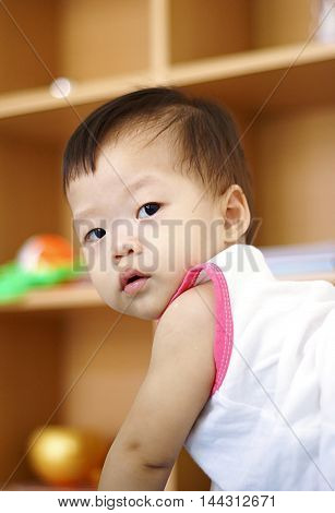 Cute Asian Baby in white dress playing in living room