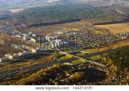 Road junction on a major highway aerial view of landscape with forests residential buildings and high speed roads. Saint Petersburg Russia