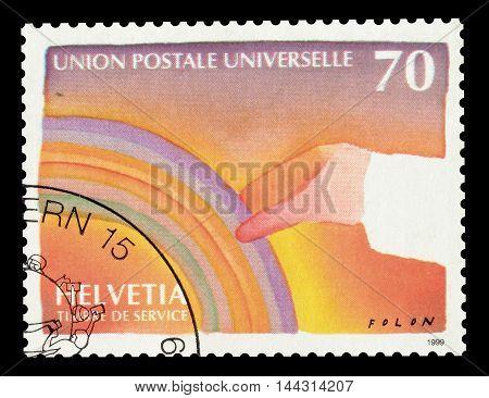 SWITZERLAND - CIRCA 1999 : Cancelled postage stamp printed by Switzerland, that shows hand holding rainbow.