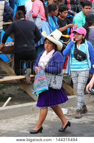 Cajamarca Peru - February 8 2016: Andean woman with sombrero and traditional dress walks in Carnival parade in Cajamarca Peru on February 8 2016