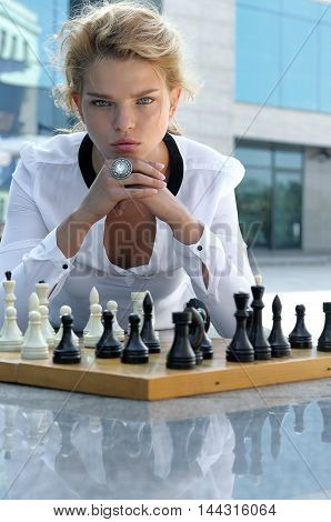 Girl Playing Chess Outdoors.