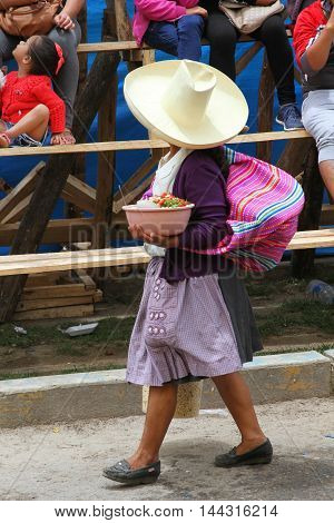 Cajamarca Peru - February 8 2016: Peruvian woman in traditional dress sells bean and tomato salad at Carnival parade in Cajamarca Peru on February 8 2016