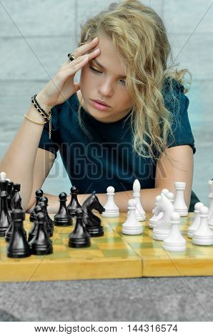 Girl Thought Sitting Near The Chess Board
