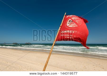 Red Warning Flag Waving in the Wind on Beach
