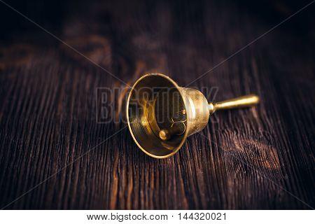 Antique brass hand bell on a dark wooden background