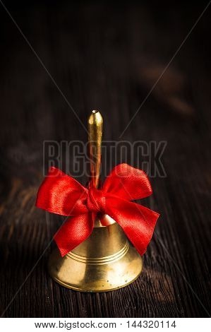 Antique brass hand bell with a red bow on a dark wooden background