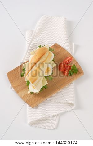 sandwich with eggs and cheese on wooden cutting board