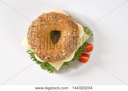 bagel sandwich with eggs and cheese on white plate