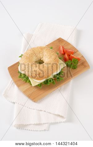 bagel sandwich with eggs and cheese on wooden cutting board