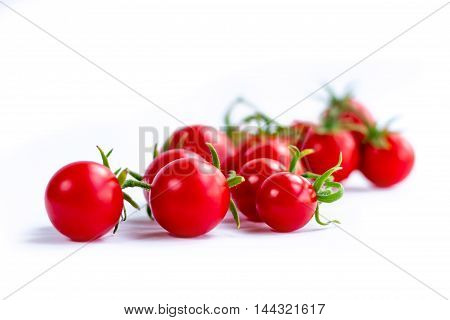 Cluster of cherry tomatoes on white background