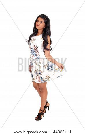 A beautiful young Indian woman standing in a summer dress with long black hair isolated for white background.