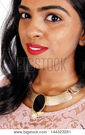 A close-up image of the face of a beautiful Indian woman with a big necklace isolated for white background.
