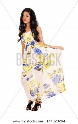 A beautiful young Indian woman in a long dress and long black hair holding up her dress isolated for white background.