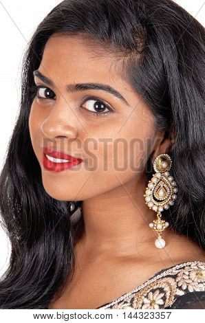 A beautiful young Indian woman's face with long black hair and earrings in closeup isolated for white background.
