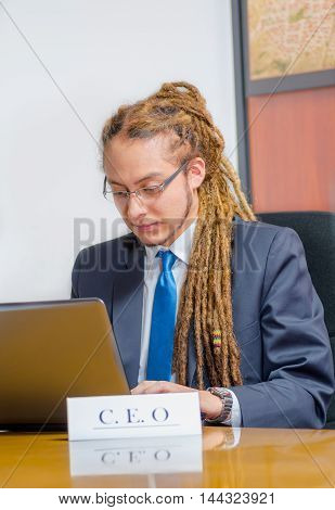 Handsome man with dreads and business suit sitting by desk looking at laptop screen working, young manager concept.
