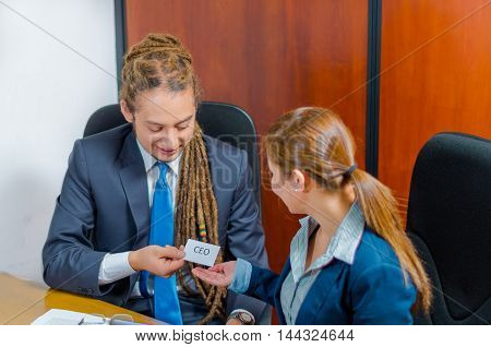 Handsome man with dreads and business suit sitting by desk next to female co-worker holding up a paper which has the word ceo written on it, young manager concept.