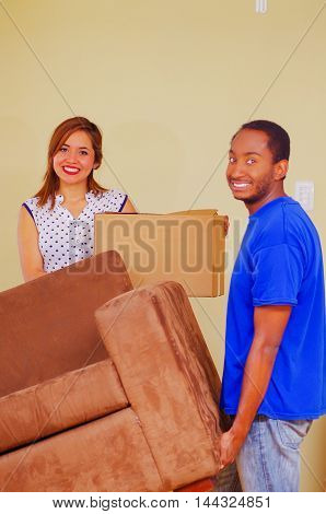 Charming interracial couple smiling to camera while lifting sofa and boxes, moving in concept.