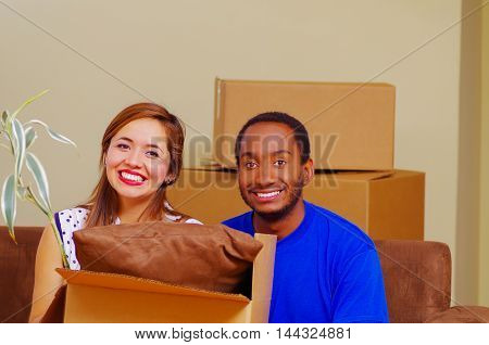Charming interracial couple smiling to camera while leaning on cardboard boxes, moving in concept.