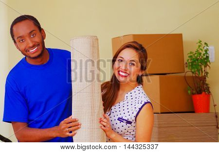 Charming interracial couple posing together, standing in front of cardboard boxes while smiling, moving in concept.