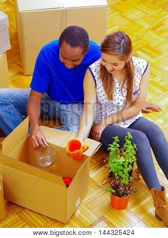 Charming interracial couple working together, sitting down and unpacking cardboard box while smiling, moving in concept.