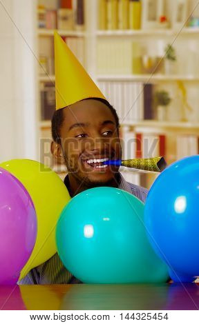 Charming man wearing blue shirt and hat sitting by table with balloons blowing party horn celebrating alone smiling.