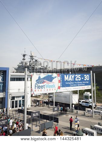 NEW YORK MAY 26 2016: Fleet Week sign at Intrepid Sea, Air & Space Museum on Pier 86N with the USS Bataan (LDH 5) amphibious assault ship moored at Pier 88 for Fleet Week NY 2016 in the background.