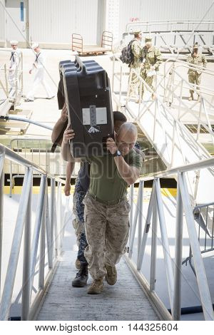 NEW YORK MAY 26 2016: Military personnel carry supplies up the gangplank to the USS Bataan (LDH 5) an amphibious assault ship moored at Pier 88 during Fleet Week NY 2016.