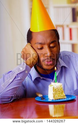 Sad man wearing blue shirt and hat sitting by table with piece of cake in front, looking depressed, celebrating alone concept.