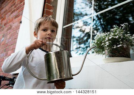 boy watering white flower in a pot