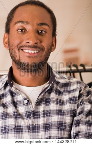 Headshot young man smiling to camera, standing in front of clothing rack, fashion concept.