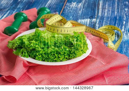 Fitness composition of lettuce on white plate weights and ruler