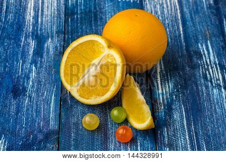 Still life composition of oranges and candies on blue wooden background