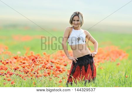 young beautiful woman on cereal field with blooming poppies