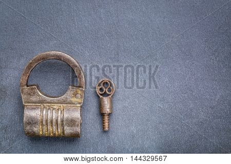 Vintage round shape hand crafted screw type iron padlock with a key on gray slate stone with a copy space