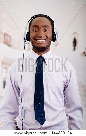Handsome man wearing headphones with microphone, white striped shirt and tie, posing interacting working for camera.