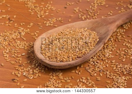 Gold linseed into a spoon over a wooden table