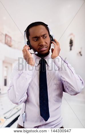 Handsome man wearing headphones with microphone, white striped shirt and tie, interacting actively, business concept.