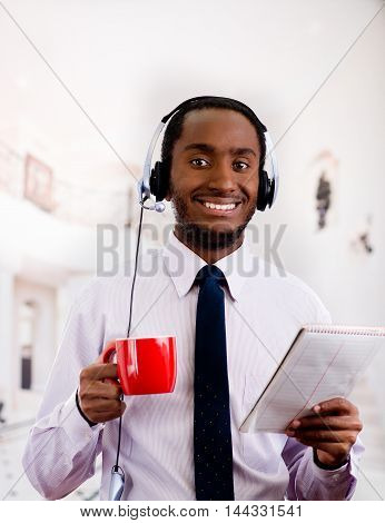 Handsome man wearing headphones with microphone, white striped shirt and tie, holding coffee mug, smiling to camera, business concept.