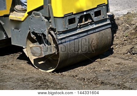A large yellow packer at a construction site rolling over sand and dirt.