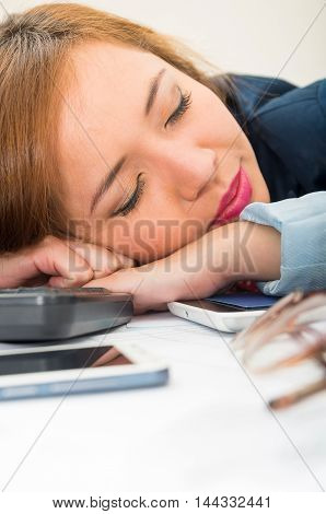 Office woman bent over white desk resting or sleeping with computer keyboard, glasses and mobile spread out.