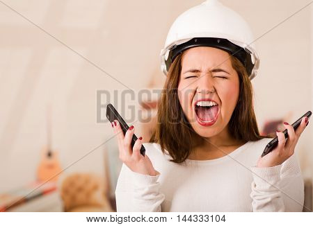 Young woman wearing construction helmet facing camera, holding two mobile phones and screaming out in frustration.