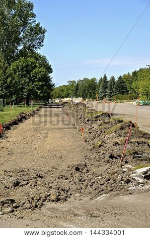 A sidewalk has been torn out and is ready for forms and new concrete.