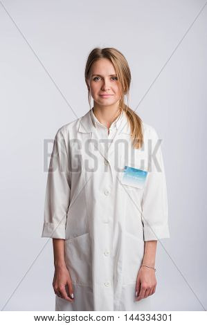 Nurse or young doctor standing and looking at camera. Isolated on white background