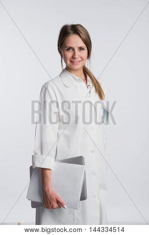 Woman doctor with papers and laptop isolated on the white.